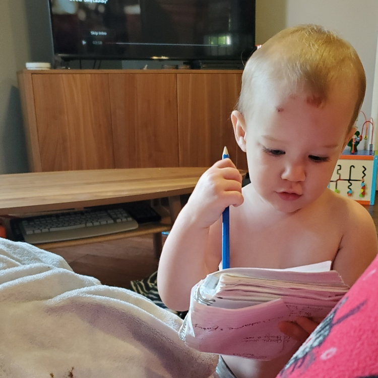 Toddler, clad only in her diaper, with a pencil and notebook in hand, looking to be erasing notes on the page.