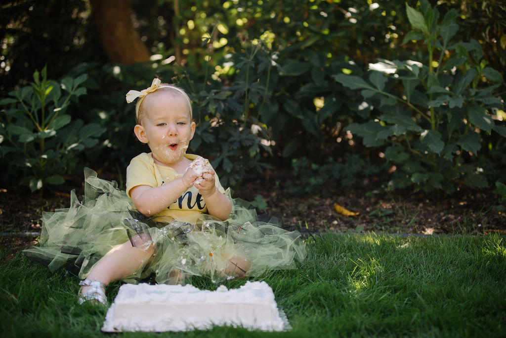 """One year old in yellow top and tulle skirt, with cake on and in her hands and on her face, and a large sheet cake is in front of her. Child has an expression of """"wow"""" on her face."""
