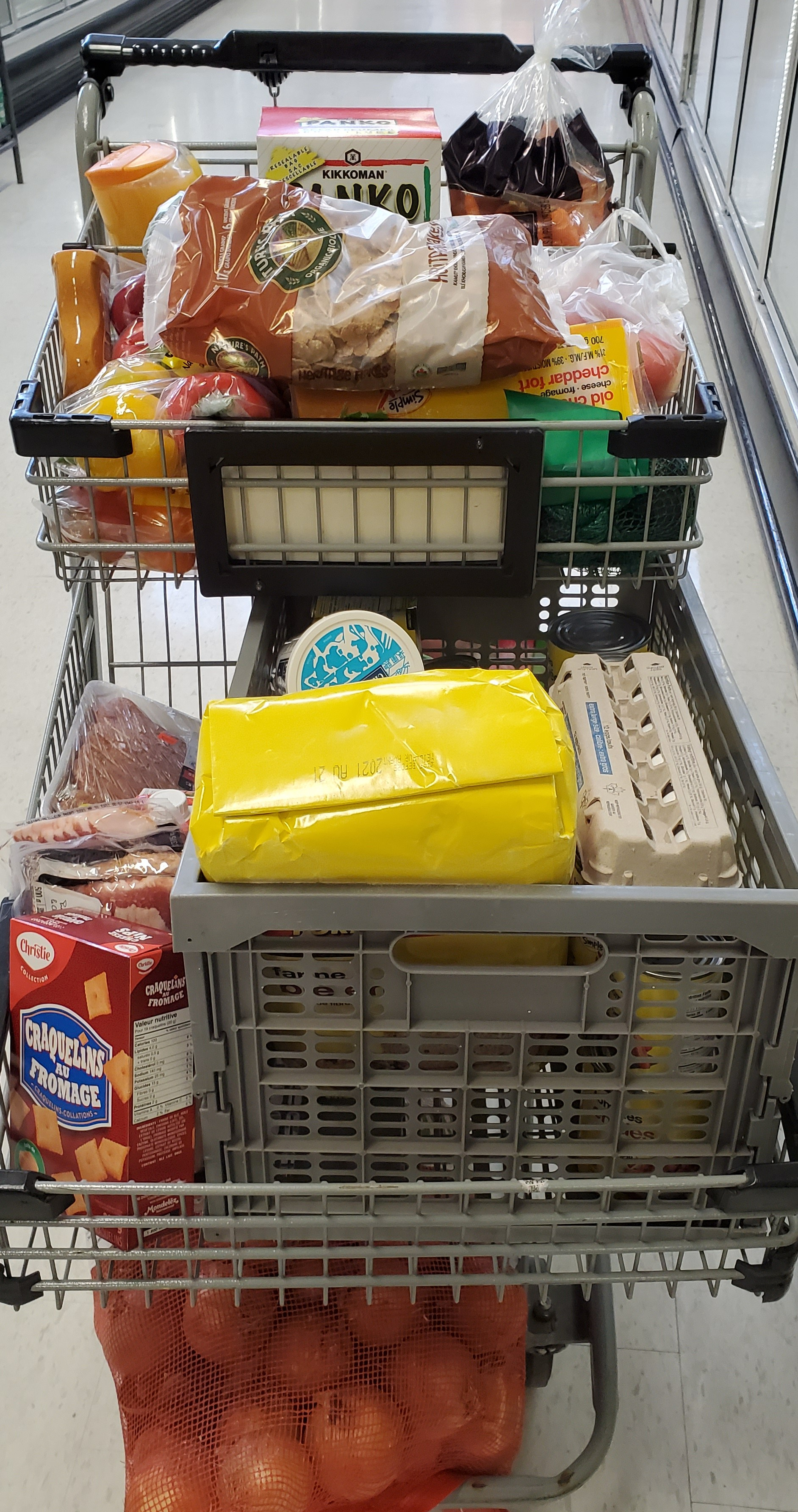 A two tier cart full of various items, including onions on the very bottom above the wheels